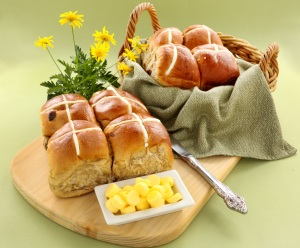 Hot cross buns in a basket and some with butter and daisies.